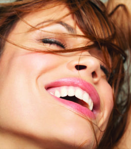 A smiling woman with bright white teeth and closed eyes.